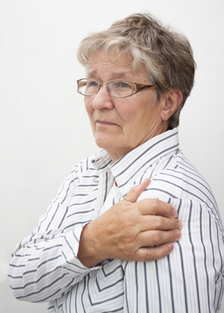 A retired pensioner lady rubbing her painful shoulder