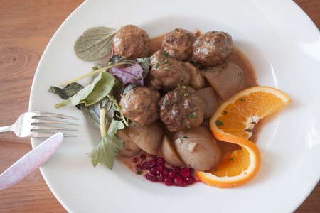 Traditional swedish meatballs served in a five star restaurant wtih orange as decorations photo