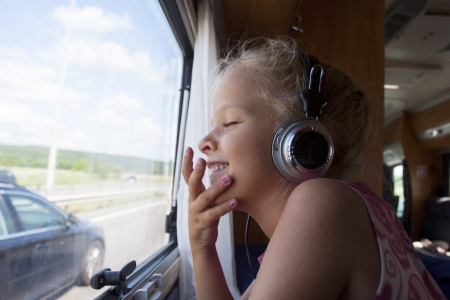 A happy girl with eyes closed sits by window in moving trailer with headphones on Stock Photo