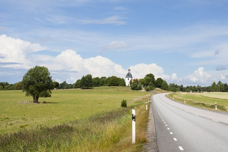 A road in Sweden leading past fields and a church photo