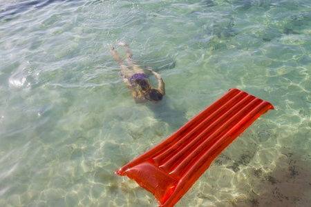 A teenager free diving towards an inflatable air mattress photo