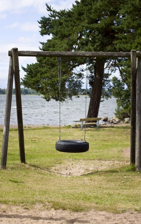 An empty swing by a lake Stock Photo - 22115248
