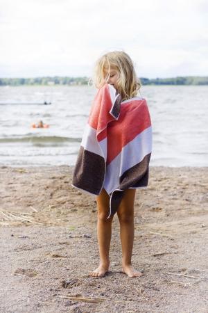 piedi nudi di bambine: Una bambina avvolta in un asciugamano dopo una nuotata in spiaggia