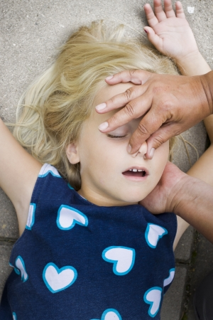 A little girl receiving mouth to mouth first aid by nurse or doctor or paramedic Stock Photo