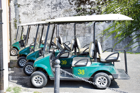 Green golf carts parked outside a country club in Italy