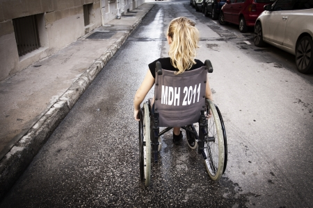 A girl sitting in a wheelchair with her back to the camera Stock Photo