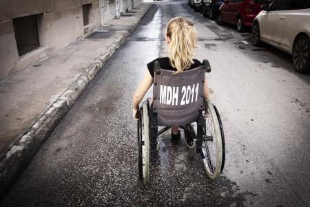detras de: Una niña sentada en una silla de ruedas, de espaldas a la cámara