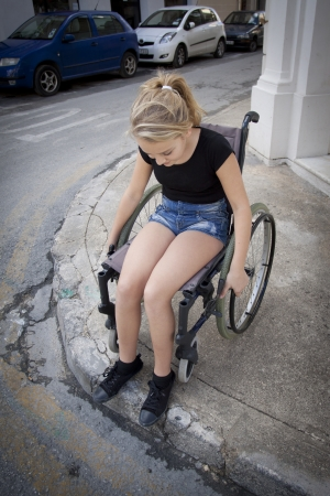 footpath: A girl in a wheelchair on the sidewalk or pavement trying to cross the road