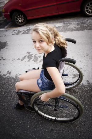 young: Cute disabled girl riding a wheelchair on the road