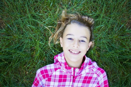 Teenage woman with checked pind white hoodie lying back on green grass, laughing and looking at the camera. Candid shot, real people Stock Photo - 23841847