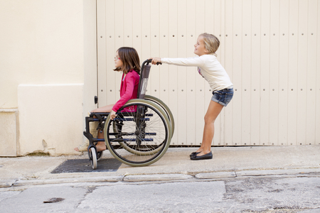 A young girl pushing her friend with a broken leg who sits in a wheelchair