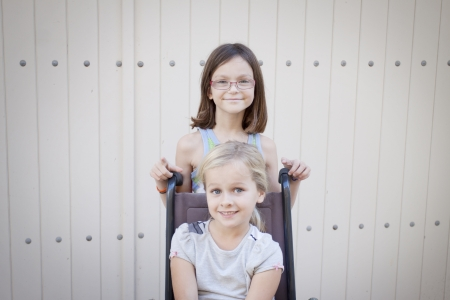 Two young children, one in a wheelchair, space for text
