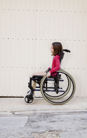 A young girl sitting outside on the sidewalk or pavement in a wheelchair with a broken leg in a cast photo