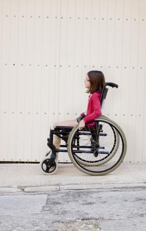 pierna rota: Una niña sentada en la acera o pavimento en una silla de ruedas con una pierna rota en un yeso Foto de archivo