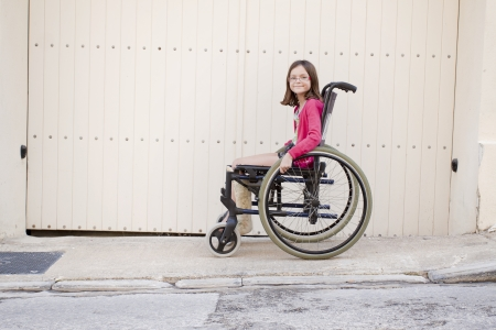 Young girl with broken leg in cast sitting on the sidewalk or pavement in a wheelchair looking at the camera. Positive feeling, space for text photo