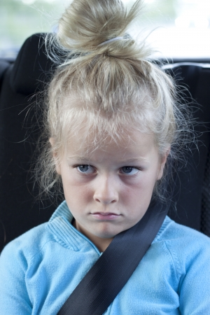buckled: A sulky child in the back of the car with seatbelt on