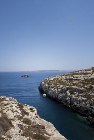 snorkle: Gozo,Maltese coastline with the cliffs,gold rocks over the sea in Malta island with the blue clear sky background Stock Photo