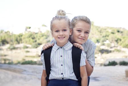uniforme escolar: Dos niñas de la escuela rubia con bolsa de la escuela y los uniformes escolares