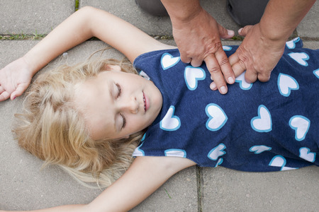 A little girl receiving first aid heart massage by nurse or doctor or paramedic Stock Photo