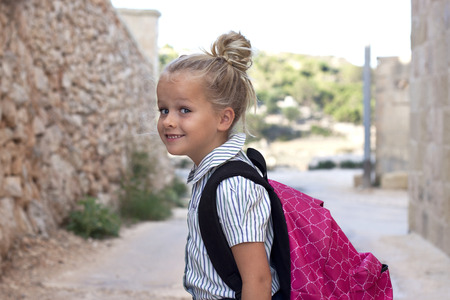 ruck sack: A young child with school uniform and bagpack outside, smiling, positive, looking at camera