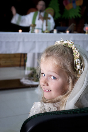 A young child doing her catholic first holy communion attending mass wtih a priest by the altar photo