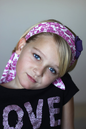 innocense: Close up of a 10 year old child looking at camera, with pink head scarf. Soft focus, space for text