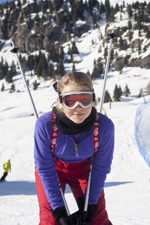 Child with ski poles in the skiing slopes photo