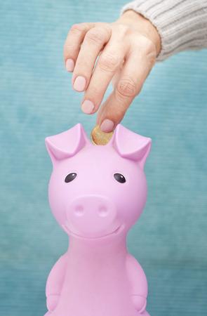 A hand dropping a euro coin into a pink piggy bank saving box photo