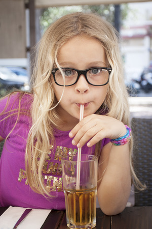 A 8 year old girl with black glasses drinking with a straw photo
