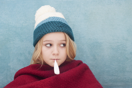 Close up of child with fever thermometer, wrapped in blanket, Space for text photo