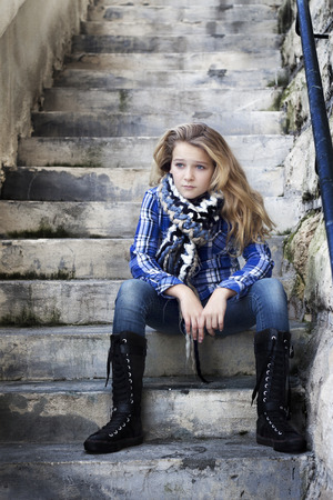 A teenager wtih attitude in cool funky clothes with high boots sitting on stairs, looking confused Stock Photo