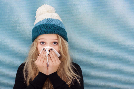 Woman with cold, blowing her nose into a tissue