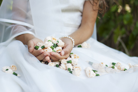 Close up of a bride or a girl doing her first holy communion holding small rose buds.