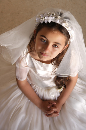 somber: Child doing her first holy communion dressed in white dress and veil, looking at camera, praying