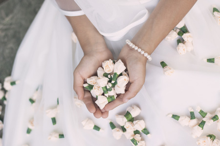 Close up of a bride or a girl doing her first holy communion holding small rose buds. Vintage, washed out look, soft filter Stock Photo