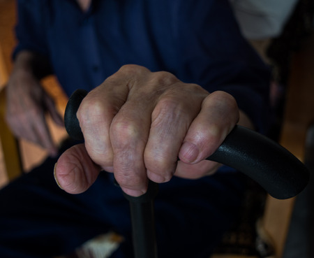 The old mans hand on a walking stick. Blurred silhouette of a man sitting in the background. Stock Photo