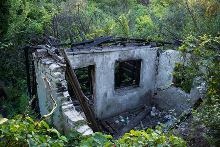 The remains of the burnt house in the woods. Desolation. View from above. Stock Photo