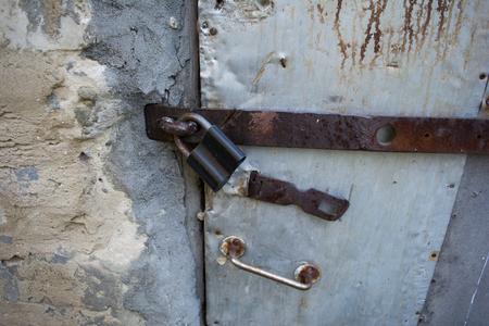 door bolt: Old dirty door closed on padlock. Bolt, door handle.