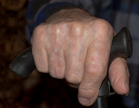 incapacitated: Hand of old, worn knob of his cane. Close-up. Stock Photo