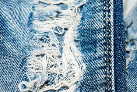 holey: Holey jeans. Blue denim texture. Threads, seam. Close-up. Stock Photo