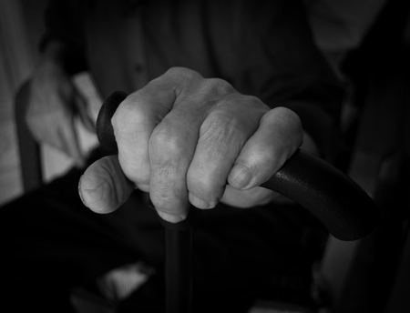 incapacitated: Hand old man on a plastic stick. Blurred background. Black and white photo.