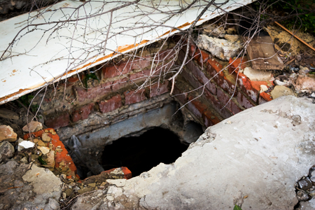 Ruins of destroyed house. Abandoned earthen cellar. Rectangular photo. Stock Photo
