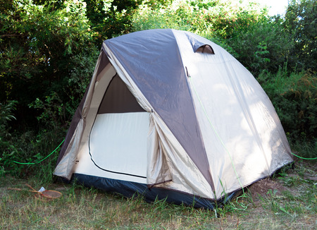 Single tent standing in the forest. Horizontal photo.