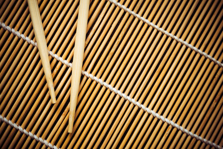 Bamboo mat and chopsticks for sushi. View from above. Rectangular horizontal photo. Фото со стока