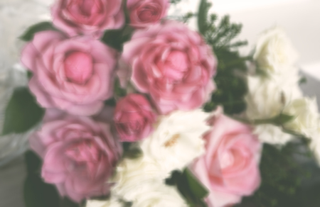Blurred rectangular photo with bouquet of white and pink roses. Cute floral background with blur.