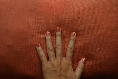 Retro Manicured Hand with Orange Nail Polish Fanning on Orange Cushion