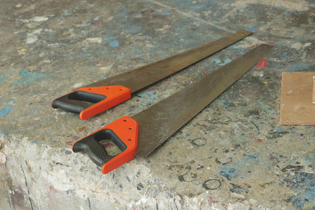 Couple of Saws on Colorful Dirty Floor - Garage Junkyard Home Backyard