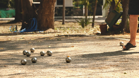Petanque Balls and Orange Wooden Ball on Sandy Ground with a Man Standing in the Shade - Sunny Day in the Park