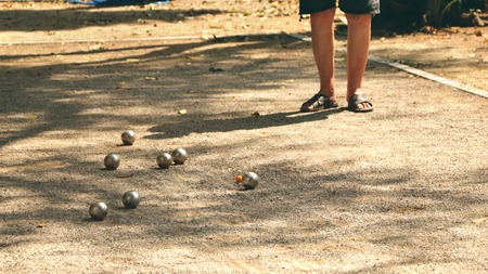 Playing Petanque in the Park - Metal Balls and Orange Wooden Ball on Rock Yard with a Man Standing in the Sun Stock Photo