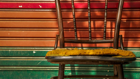 Abandoned Vintage Metal Chair with Colorful Roller Shutter Door Corrugated Iron Background. Outdoor Garage Junkyard. Street Photography. Bangkok, Thailand.